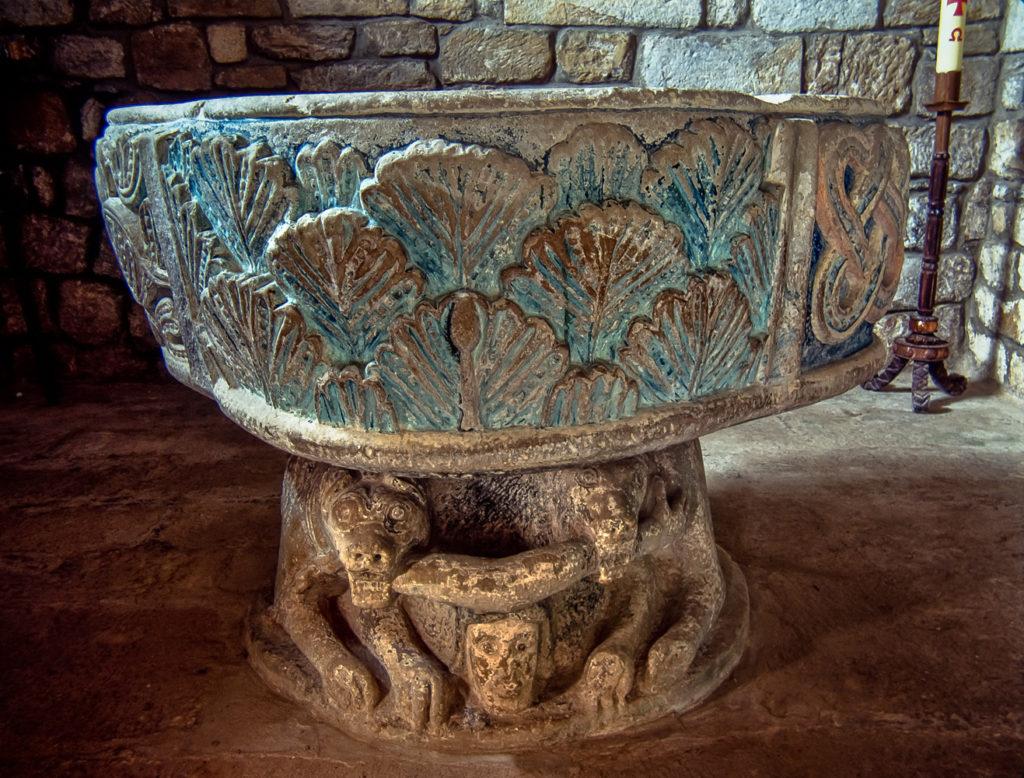 Pila bautismal de la iglesia de Santa Maria en la localidad cántabra de Bareyo con dos leones androfagos en la base de la copa