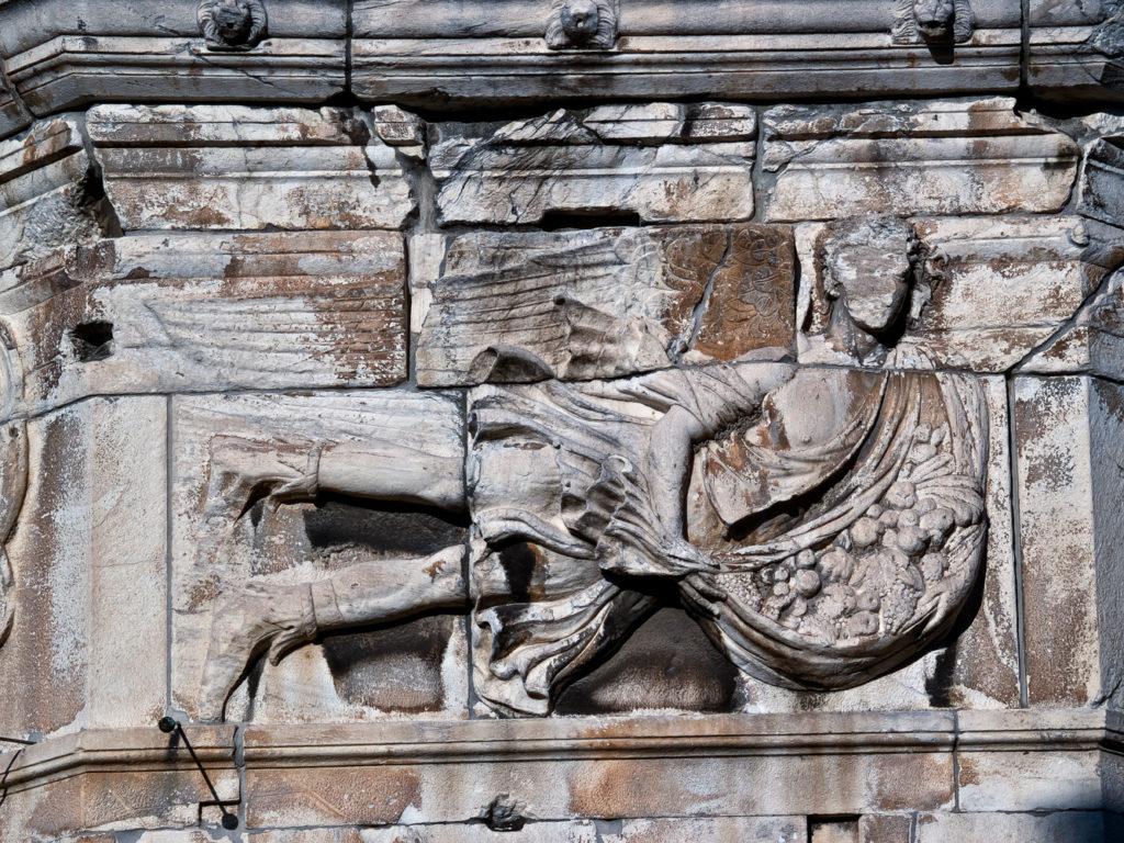 Apeliotas el viento del este es representado en la Torre de los Vientos como un joven llevando frutas y granos